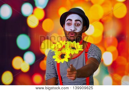 Headshot pantomime man with facial paint posing for camera holding sunflowers in hands, blurry lights background.