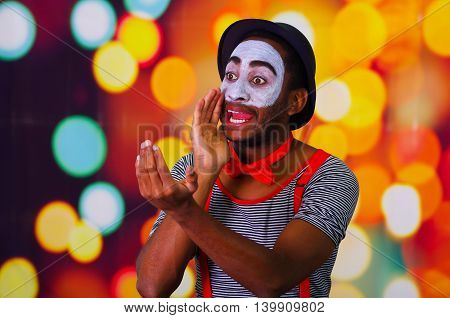 Pantomime man with facial paint posing for camera holding blowing horn, blurry lights background.