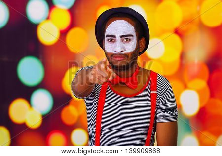 Pantomime man wearing facial paint pointing into camera, standing with arms crossed, blurry lights background.