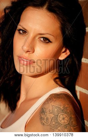 Beautiful brunette woman with tight shirt on red brick wall background