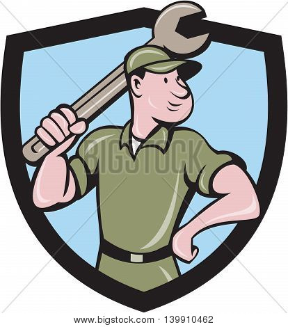 Illustration of a mechanic wielding holding spanner wrench looking to the side with one hand on hips viewed from front set inside shield crest on isolated background done in cartoon style.