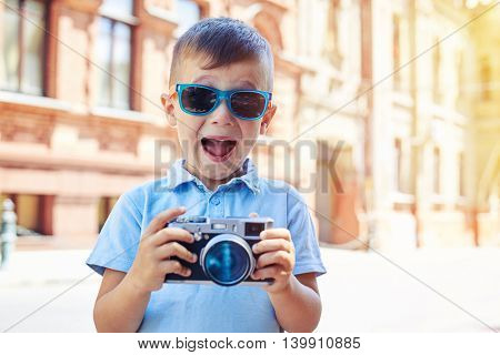 Small boy in sunglasses is making excited face while holding a photo camera and trying to take a shot during walk in historical part of the city