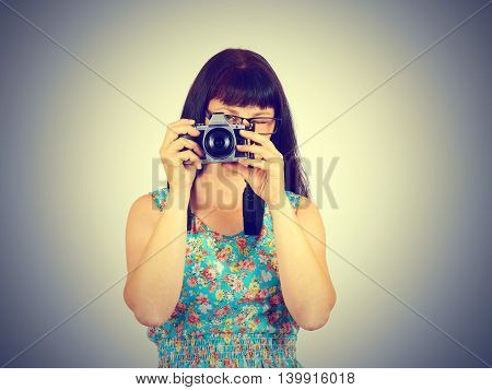Young Woman Wearing Glasses Taking Pictures On The Retro Camera