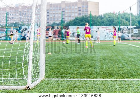 goalkeeper woman stands against goal with net and stadium. female soccer player diving to catch the ball. sporty girl