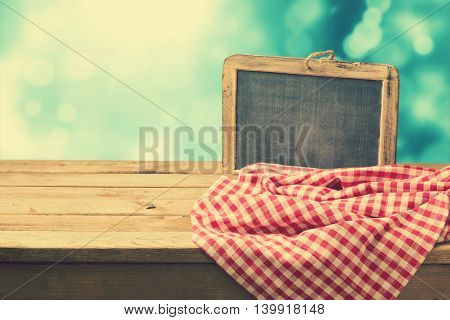Retro background with chalkboard and tablecloth on wooden table