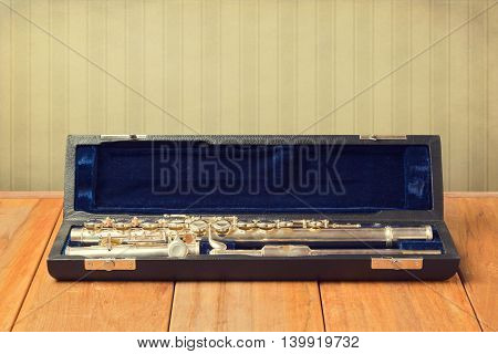 Musical instrument flute in carrying case on wooden table