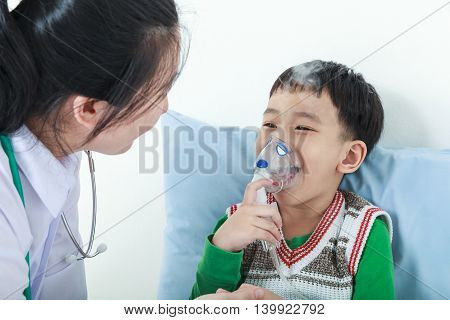 Happy child having respiratory illness helped by health professional with inhaler. Pediatrician take care asian boy with asthma problems making inhalation with mask on his face at hospital.
