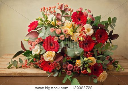 Beautiful flower bouquet on wooden table over grunge background