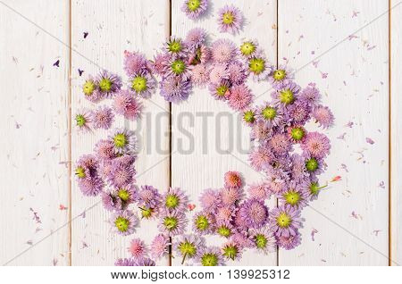 Beautiful circlet of purple aster flowers on white wooden background. Delicate floral composition with free space in center of wreath