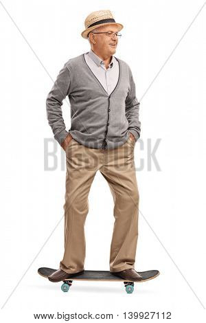 Full length portrait of a senior man riding a skateboard isolated on white background