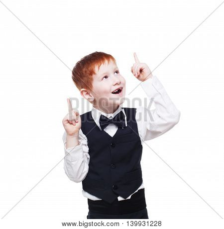 Little cute happy redhead boy in vest with bow tie has an idea. Portrait of well-dressed emotional child show finger up as eureka sign, isolated on white background