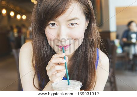 young woman drinking iced coffee in coffee shop