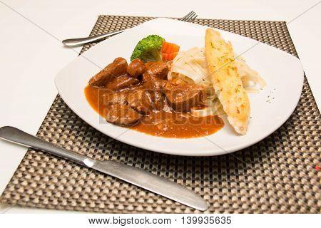 Pork stew with pasta on a white background