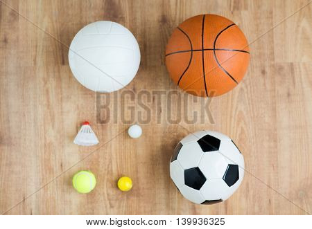 sport, fitness, game, sports equipment and objects concept - close up of different sports balls set and shuttlecock on wooden floor from top