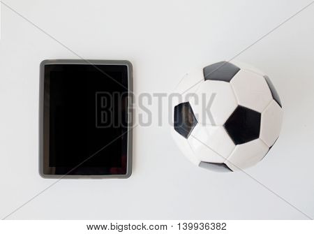 sport, football, technology and sports equipment concept - close up of soccer ball and tablet pc computer with black blank screen over white background from top