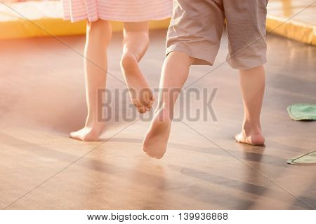 children's feet running across the trampoline outdoors in the summer