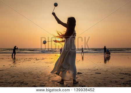 Arambol, Goa - February 13, 2016: Beautiful unidentified woman dancing at sunset at Arambol beach in Goa, India.