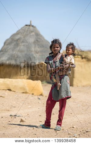 Jaisalmer, India - March 14, 2016: Unidentified tribal girl holding a baby in traditional village in Tar desert near Jaisalmer, India.