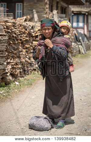 Pisang village, Nepal - May 5, 2016: Portrait of an unidentified tibetan woman with a baby in the Himalayas mountains in Lower Pisang village, Nepal. Annapurna Circuit Trek