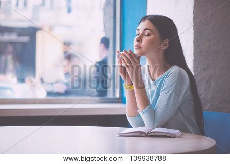 Just relax. Delighted and content young woman smelling nourishing coffee with shut eyes while being in a cafe