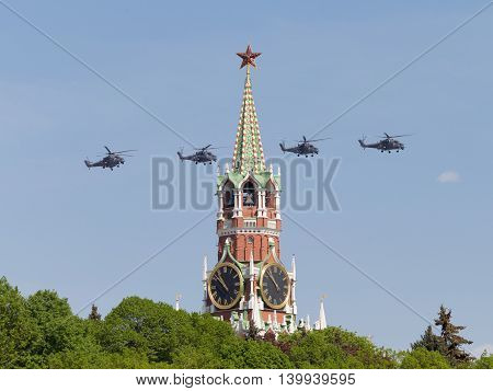 Moscow - May 9 2016: Four gray powerful military helicopters Mi-35 flying on the background of the Spasskaya Tower of the Kremlin during Victory Day parade May 9 2016 Moscow Russia