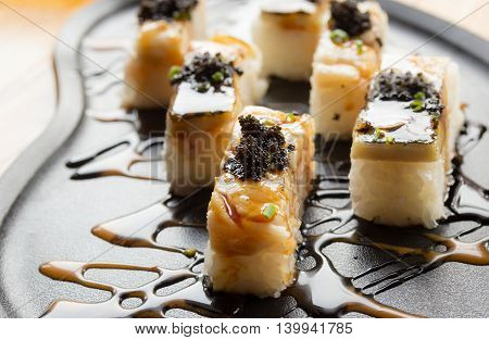 Grilled mackerel or saba sushi with black fish roe on plate poster