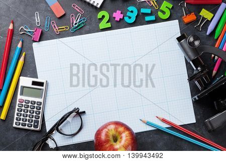 School and office supplies in front of chalk board. Back to school concept with copy space