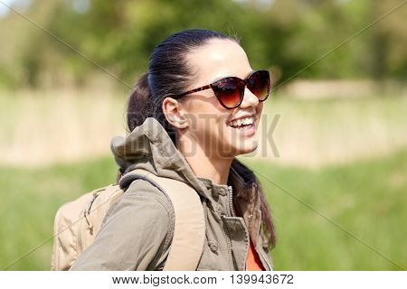 travel, hiking, backpacking, tourism and people concept - happy young woman in sunglasses with backpack walking along country road outdoors