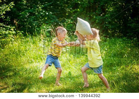 Children Fighting Together With Pillows In A Sunny Summer Garden