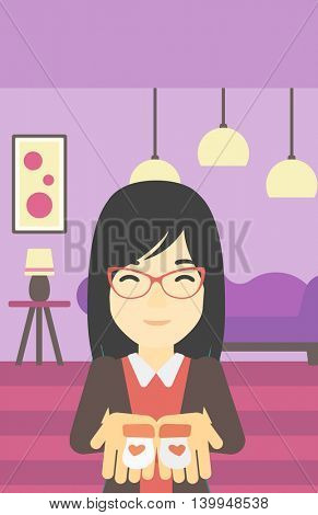 An asian pregnant woman holding baby booties in hands on the background of living room. Vector flat design illustration. Vertical layout.