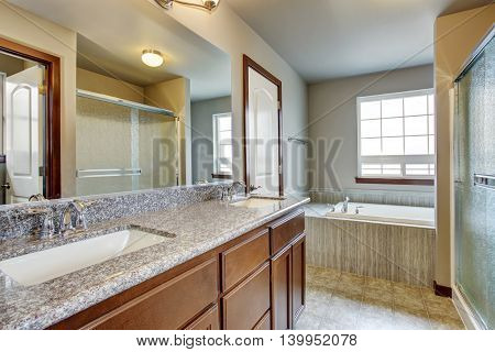 Lovely Bathroom Interior With Vanity Cabinet, Large Mirror And Bathtub With Tile Trim.