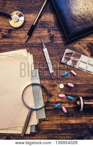 Assorted office supplies on doctor's desk. General medical practitioner workspace top view.
