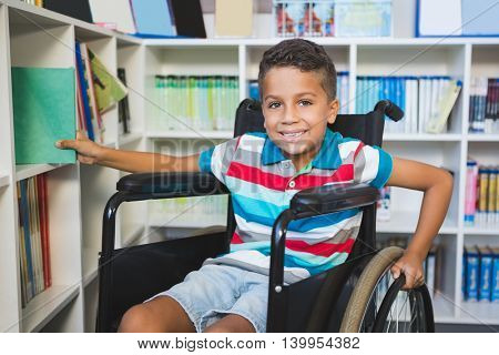 Portrait of disabled boy selecting a book from bookshelf in library at school