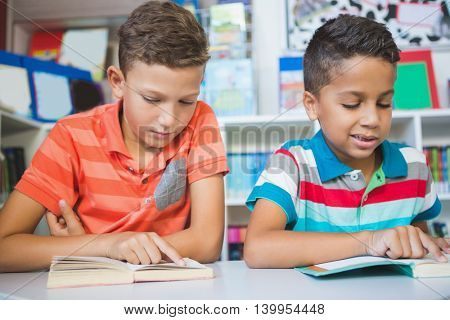 Schoolkids reading book in library at school