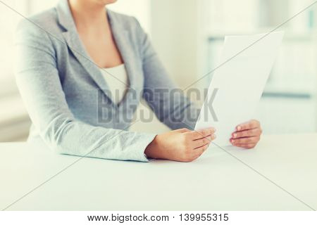 business, finance and people concept - close up of woman reading papers or tax report at office