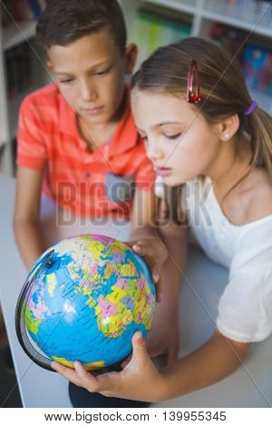 Schoolkids studying globe in library at school