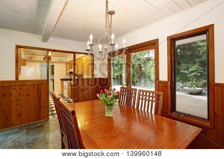White And Brown Dining Room With Fresh Flowers On The Table Set And Walls With Wooden Plank Trim.