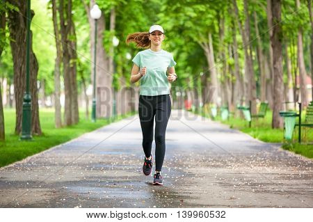 Full Length Portrait Of A Female Runner Running In The Park.
