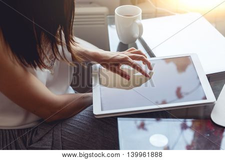 Closeup of brunette woman using tablet in cafe. Image with lens flare effect and split toned