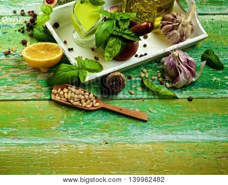 Freshly Made Creamy Pesto Sauce in Glass Gravy Boat with Ingredients Spices and Olive Oil in White Wooden Tray as Frame on Cracked Wooden background