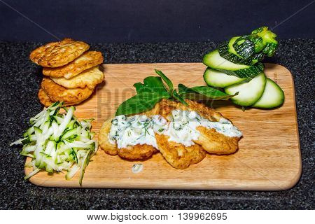 zucchini pancakes on a dark background. Making strips zucchini and young zucchini with slice isolated on black background.