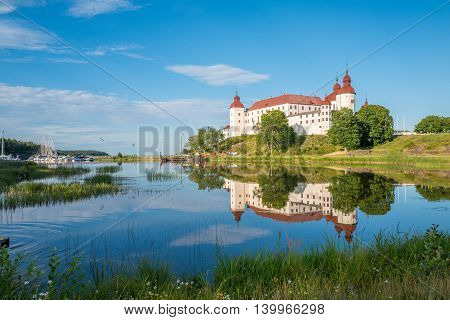 LIDKOPING, SWEDEN - JULY 23, 2016: Summer evening by Lake Vanern and Lacko Castle. Lacko Castle is considered as one of the most beautiful castles in Sweden.