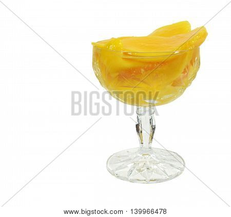 Compote mangoes in crystal ramekin on high legs, isolated on white background