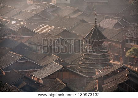 Tile roofs of wooden houses of Chinese peasants in the village of Dong ethnic minority in southwest China early misty morning spring, Zhaoxing Dong Village Guizhou Province China.