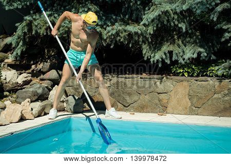 young handsome macho man cleaner with athletic muscular fit sexy body working at swimming pool deck cleaning blue water sunny day outdoor at summer