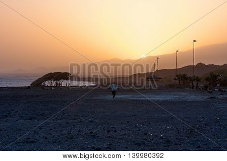 PORTO NOVO CAPE VERDE - DECEMBER 09, 2015: Amazing sunset evening at the beach of Santo Antao Island. People walking and watching the sun