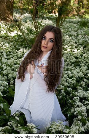 Beautiful Young Woman In A Forest With Her Arms Crossed Against Her Chest