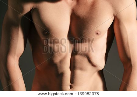 Muscular torso pecs abs and arms of male bodybuilder close-up
