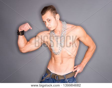 Closeup of a shirtless muscular man posing with chains around his neck and showing his tense biceps