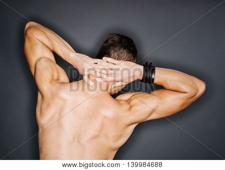 Back of a muscular man's perfect trapezius and triceps